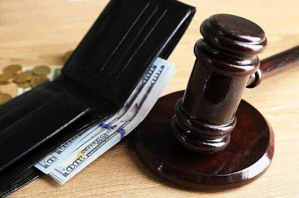 Open wallet with cash from settlement with judges gavel
